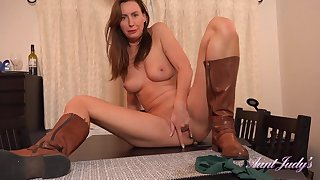 British dominatrix Lara Latex masturbating on table top in down in the mouth leather boots