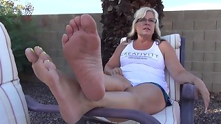 Good looking MILF exposing her tattooed feet all over jittery nail polish outdoors